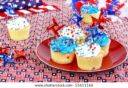 July 4th cupcakes in a festive celebratory table setting. - stock photo