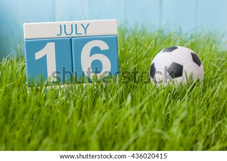 July 16th. Image of july 16 wooden color calendar on greengrass lawn background. Summer day, empty space for text