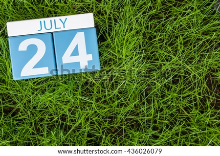 July 24th. Image of july 24 wooden color calendar on greengrass lawn background. Summer day, empty space for text