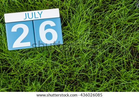 July 26th. Image of july 26 wooden color calendar on greengrass lawn background. Summer day, empty space for text