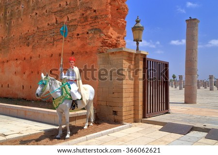 July 10, 2015: Traditional guard on a white horse near the ruins of an old mosque and Hassan Tower in Rabat, Morocco  - stock photo