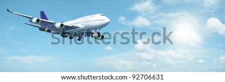 Jumbo jet aircraft is maneuvering in a sunny sky. Panoramic composition.