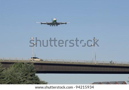 Jumbo jet  Boeing 747 landing, above highway bridge - stock photo