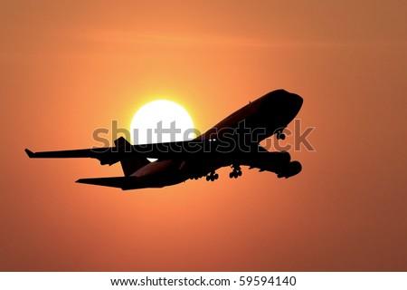 jumbo jet landing in a sunset - stock photo