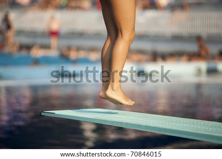 Jump. A girl preparing to jump into a swimming pool. - stock photo