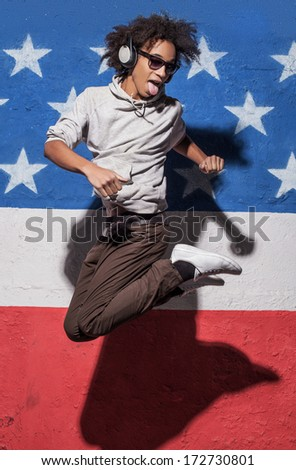Jump! Cheerful young African man in headphones jumping against American flag - stock photo