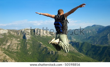 jump from cliff (regular backpack) - stock photo
