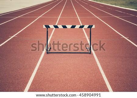 Jump hurdle on running track vintage - stock photo