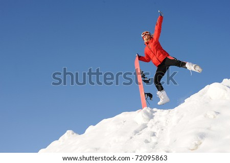 jump of happy young woman with snowboard - stock photo