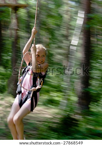 Jump of little girl from tree using rope