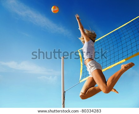 Jump of young girl, playing volleyball on beach. - stock photo