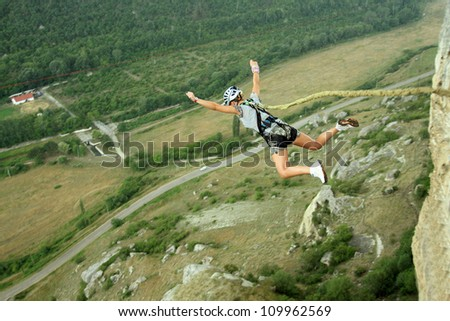 Jump off a cliff with a rope. - stock photo
