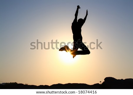 jump! silhouette of a young male jumping over sunset background