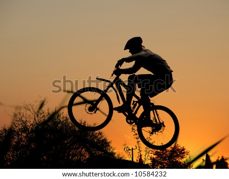 jump with a mountain bike and orange sunset - stock photo