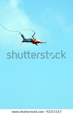 Jump with a rope from the cliff. - stock photo