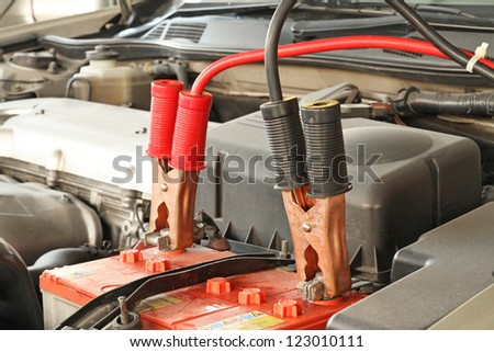 Jumper cables charging battery on a car - stock photo