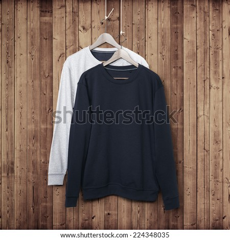 Jumpers on a dark wood wall - stock photo