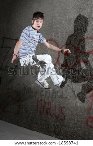 Jumping boy in front of a graffiti wall - stock photo