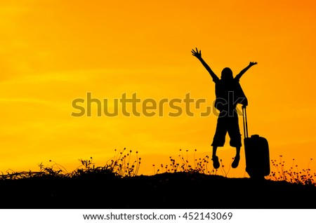 Jumping boy with a suitcase on a meadow at sunset, travel concept with copyspace - stock photo
