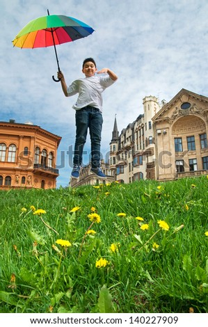 Jumping boy with umbrella - stock photo