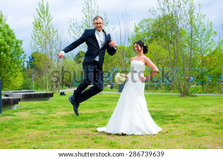 jumping bridegroom and his bride together in front of nature background - stock photo