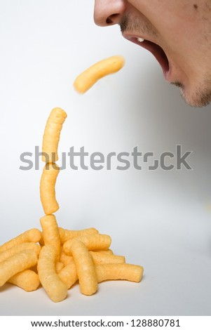 jumping chese puffs in mouth - stock photo