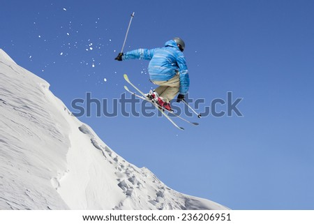 Jumping freestyle skier through air on blue sky background - stock photo