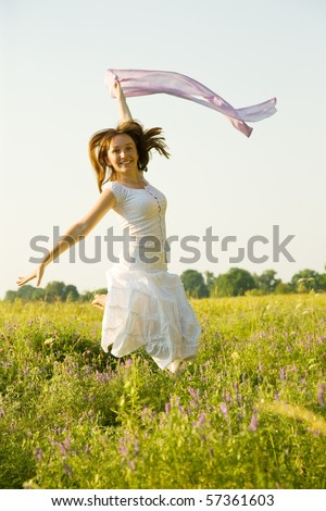 Jumping girl against summer meadow in summer day - stock photo