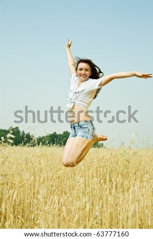 Jumping girl  at cereals field in summer - stock photo