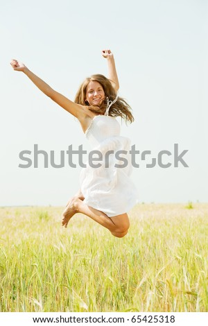 Jumping girl  at cereals field in summer