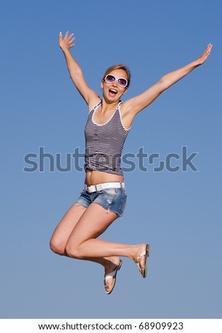Jumping girl. Attractive young woman in shorts and sunglasses jumping on background of sky