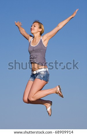 Jumping girl. Attractive young woman in shorts jumping on background of sky