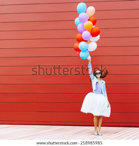 Jumping girl with colorful balloons in her hand. Warm sunny day. Outside. Red background - stock photo