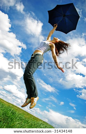 Jumping girl  with umberella on meadow - stock photo