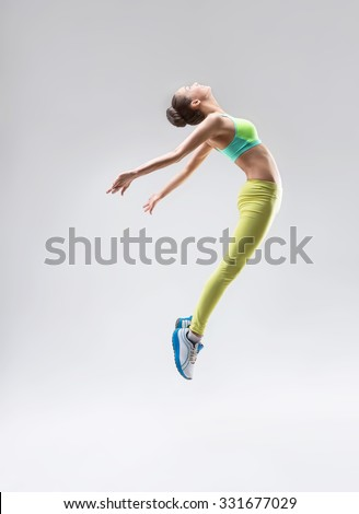 Jumping gymnast in the studio - stock photo