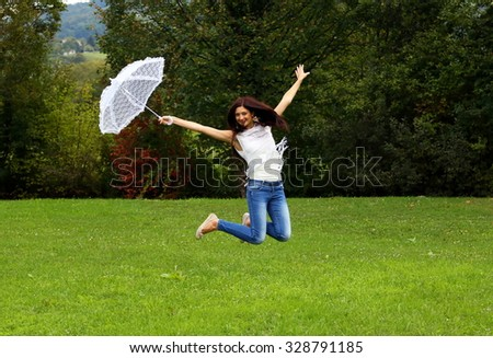 Jumping happy woman with white lace umbrella.