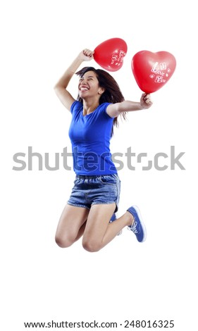 Jumping joyful young lady with heart shaped valentines' balloon. Isolated in white background. - stock photo