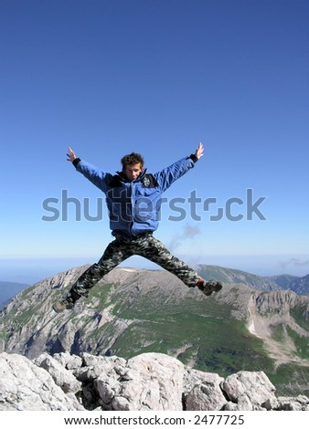 jumping man in front of mountains - stock photo