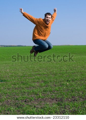 Jumping man in jeans and orange jacket on blue sky and green grass background - stock photo