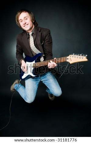 Jumping man with electro guitar, studio shot - stock photo