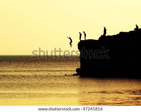 jumping of a cliff at sunset - stock photo