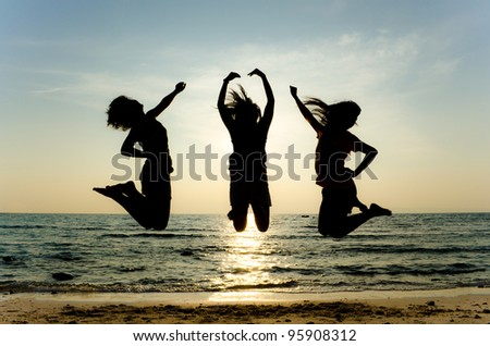 Jumping on the beach - stock photo