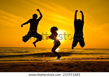 jumping on the beach so fun - stock photo