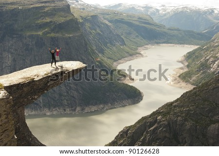 Jumping on the rock high above the fjord - stock photo