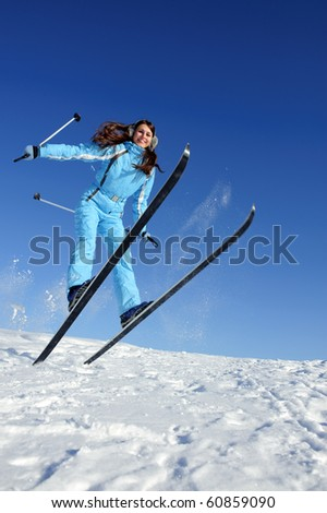 jumping pretty young woman in ski suit full of energy - stock photo