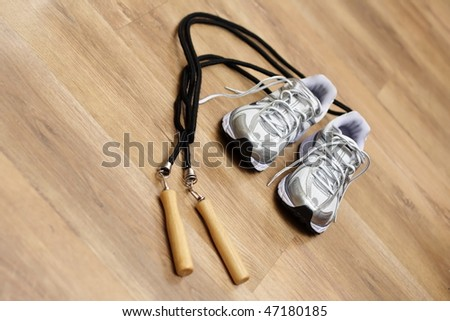 Jumping rope and trainers on a gym floor - stock photo
