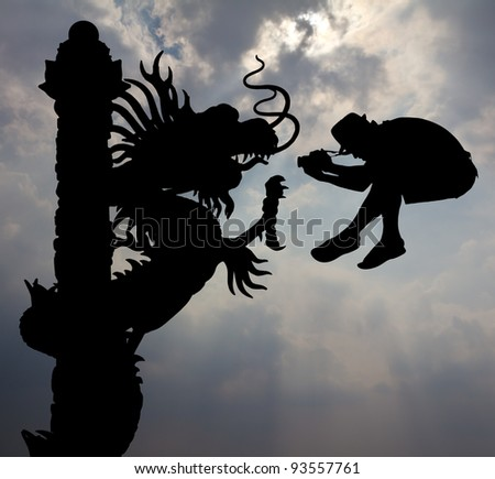 Jumping shot a dragon. Silhouette of the photographer who shot jumping dragon on the sky. - stock photo