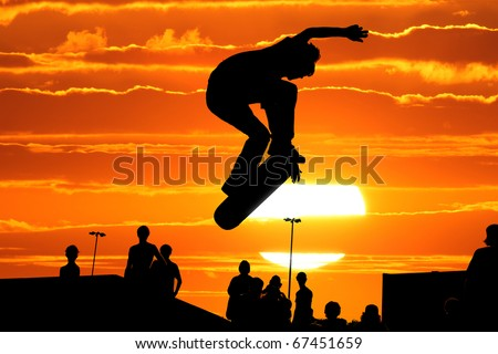 Jumping skateboarder silhouette over scenic sunset sky background - stock photo