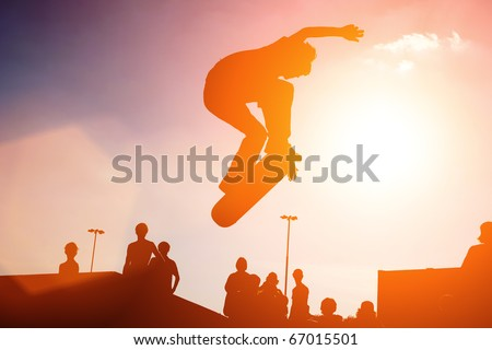 Jumping skateboarder silhouette over sunset sky background - stock photo