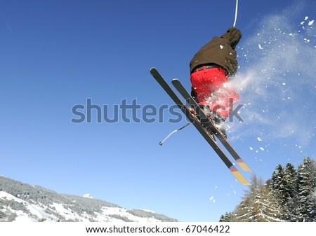 Jumping skier having fun in mountain in winter - stock photo